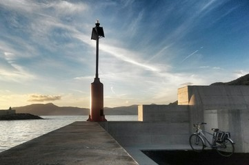 lighthouse,  dam and cycle against seascape sunset