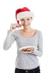 Happy woman in santa hat eating christmas cookies