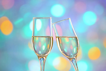 Two champagne glasses on colorful background