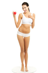 Full length woman in underwear holding heart model