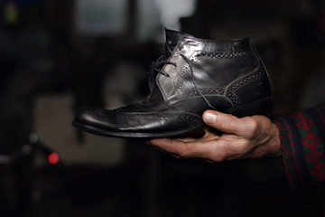Old black shoe in old man's hand