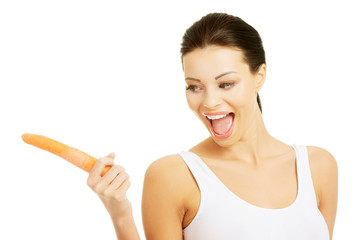 Happy young woman with a carrot