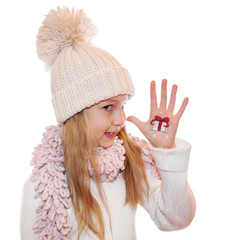 Girl demonstrating Christmas symbols, painted on hands.