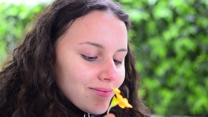 beautiful girl smelling yellow flower in springtime