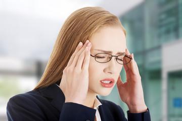 Beautiful caucasian business woman with headache.