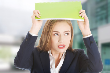 Beautiful caucasian woman is holding notebook over her head