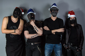 Man's metal band in christmas hats and masks