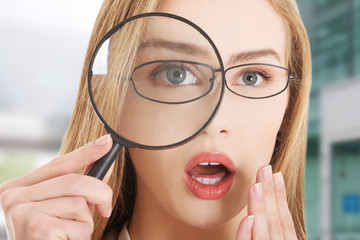 Beautiful caucasian business woman with magnifying glass.
