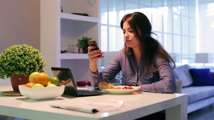 Woman typing sms and eating healthy breakfast at home