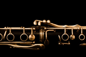 Detail of the clarinet in golden tones on a black background