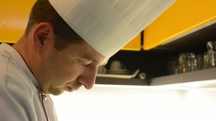 chef cooks food in the kitchen - detail of head - closeup