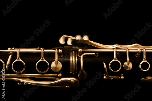 Detail of the clarinet in golden tones on a black background - 73531222