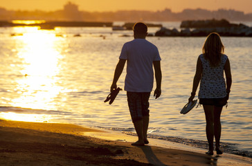 A couple Walking On Beach At Sunset