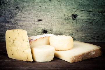 Various types of cheese on a wooden background. tinted
