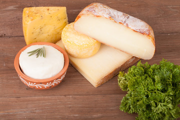 Various types of cheese on a wooden background with parsley.