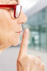 Elderly woman is having finger on her lips.