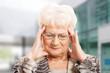 Old elegant lady is having a headache.