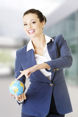 Young business woman holding small globe.