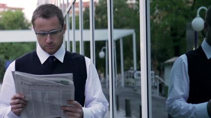 Businessman walking on street and reading newspaper, steadycam