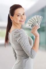 Beatiful casual woman holding money.