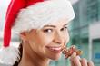 Beautiful woman in santa hat eating a cookie.