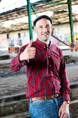 young man in checkered with thumb up