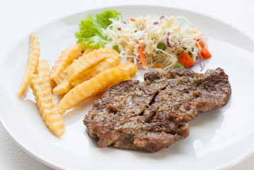 steak served with crisp golden French fries and fresh green herb