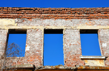 ruined brick house with windows against the sky