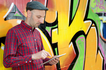 young man with tablet PC is leaning against a graffiti- wall