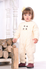 toddler girl near woodpile