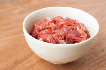 raw beef in white bowl on wooden background