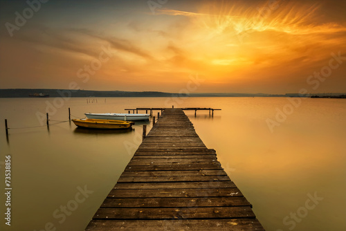 Fotobehang Zonsondergang Sunset view with boats at a lake coast near Varna, Bulgaria