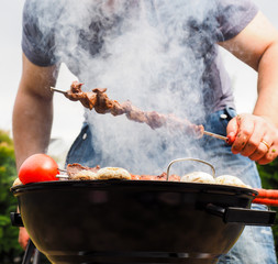 Chef covered in smoke grilling skewers of meat and vegetables ov