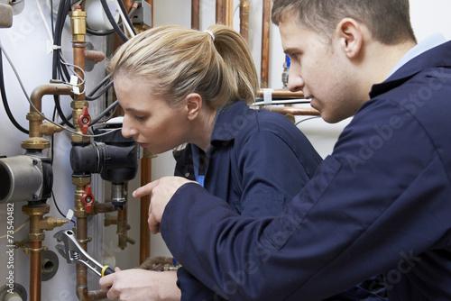 Leinwanddruck Bild Female Trainee Plumber Working On Central Heating Boiler