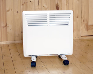 White electric convector heater in wooden house