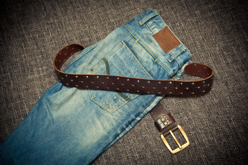 Fashionable clothes: blue jeans and leather belt with buckle
