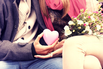 Midsection of a romantic couple sitting on a bench
