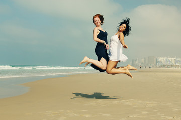 portrait of two smiling girlfriends jumping at the beach