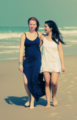 portrait of two smiling girlfriends walking at the beach