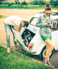 Couple in a moment of troubles during a vintage classic car trip