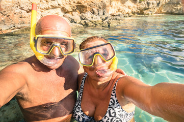 Senior happy couple taking a selfie at Blue Lagoon in Malta
