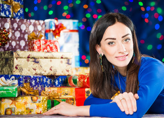 young smiling brunet at holiday gifts background