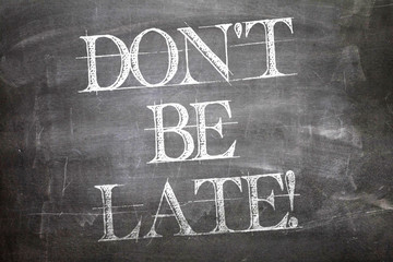 Don't Be Late written on blackboard