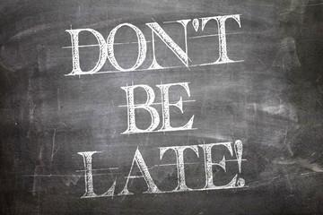Don't Be Late written on blackboard