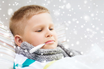 ill boy with thermometer lying in bed at home