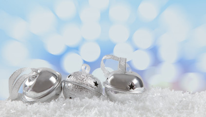 Three Jingle Bells laying on snow with light bokeh in the backgr