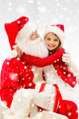 smiling girl hugging santa claus with gift at home