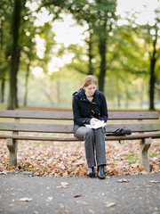 Woman Taking Notes in a Park