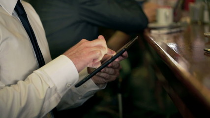 Businessman using tablet in the pub, steadycam shot