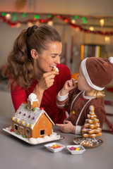 Happy mother and baby eating cookie in christmas kitchen
